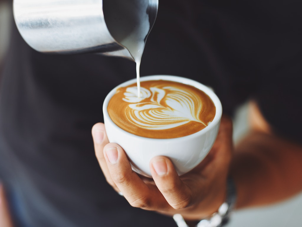a barista finishes a latte