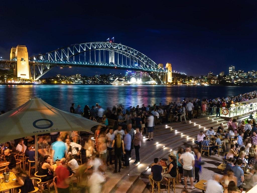 people enjoying dinner at a riverside restaurant