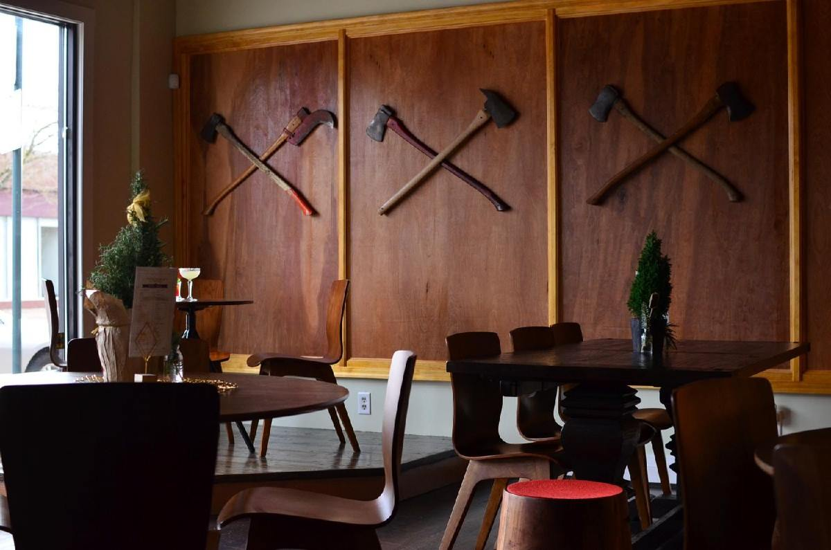 dining tables and axes displayed on the wall at overlook odge