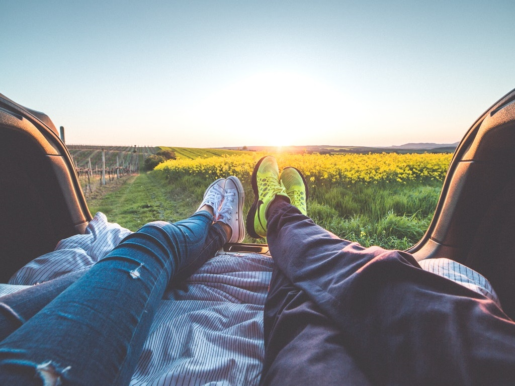 a couple laying on a picnic blanket on a date