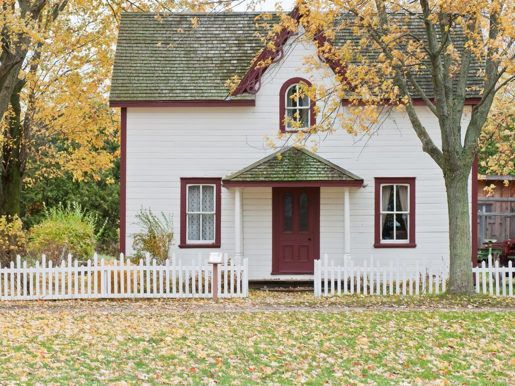a quaint home with a white picket fence in the fall
