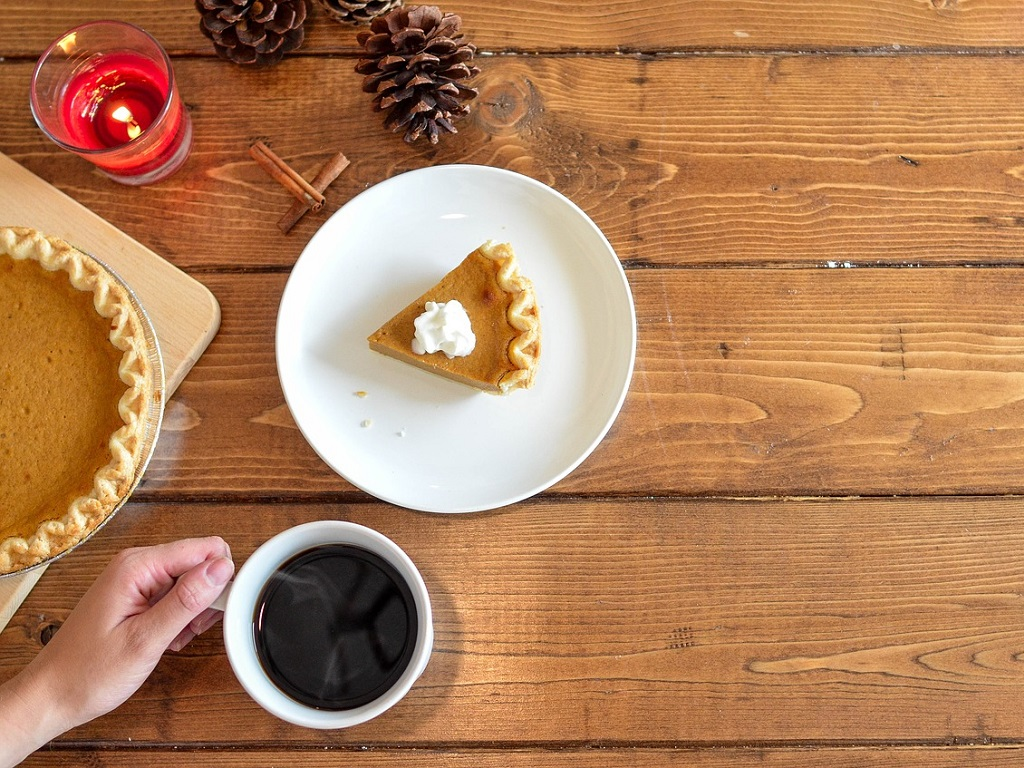 a table with pumpkin pie and coffee