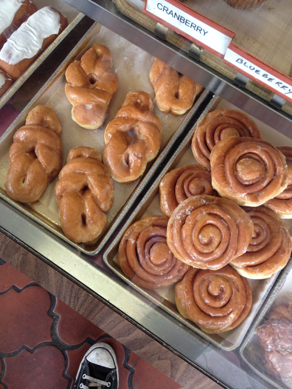 cinnamon rolls and other pastries behind glass