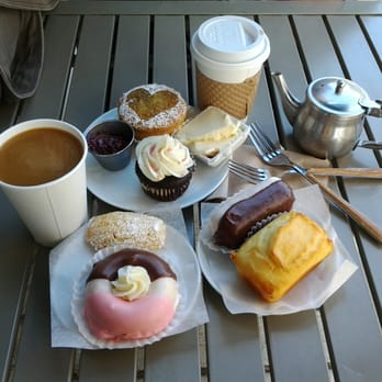 table with coffee, donuts, cupcakes, and other pastries on top
