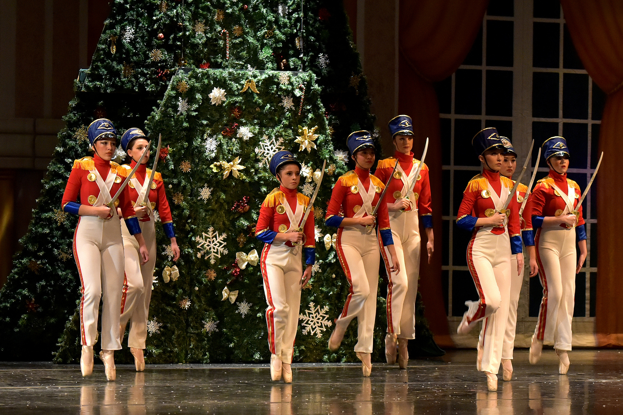 holiday soldiers dance in front of christmas tree for holiday performance