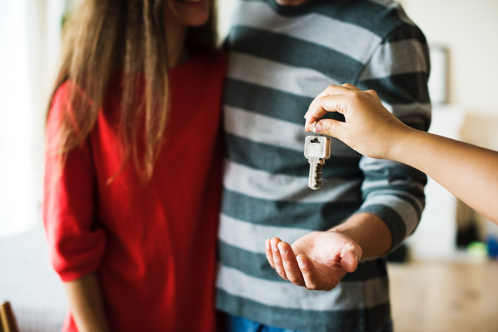 real estate agent handing over key to new home owners