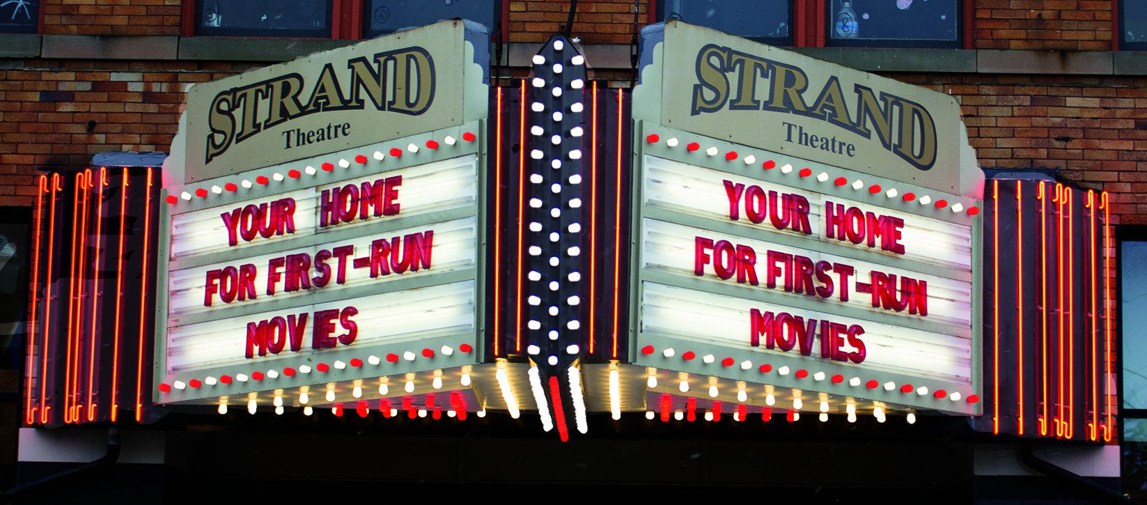 outside of Strand Theatre with old school movie theater sign