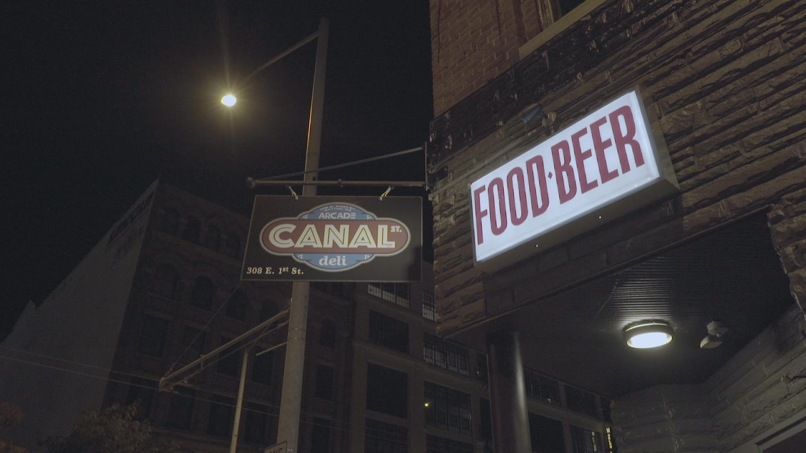 Canal Street Arcade & Deli sign next to a food & beer sign