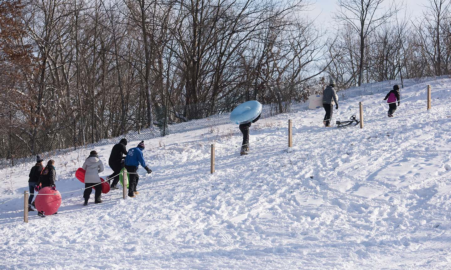 people walking up snow covered hill with sleds & tubes at a Cleveland Metro Park