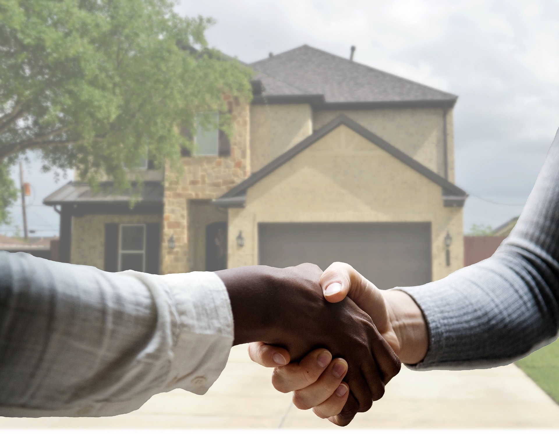 two people shaking hands in front of a home