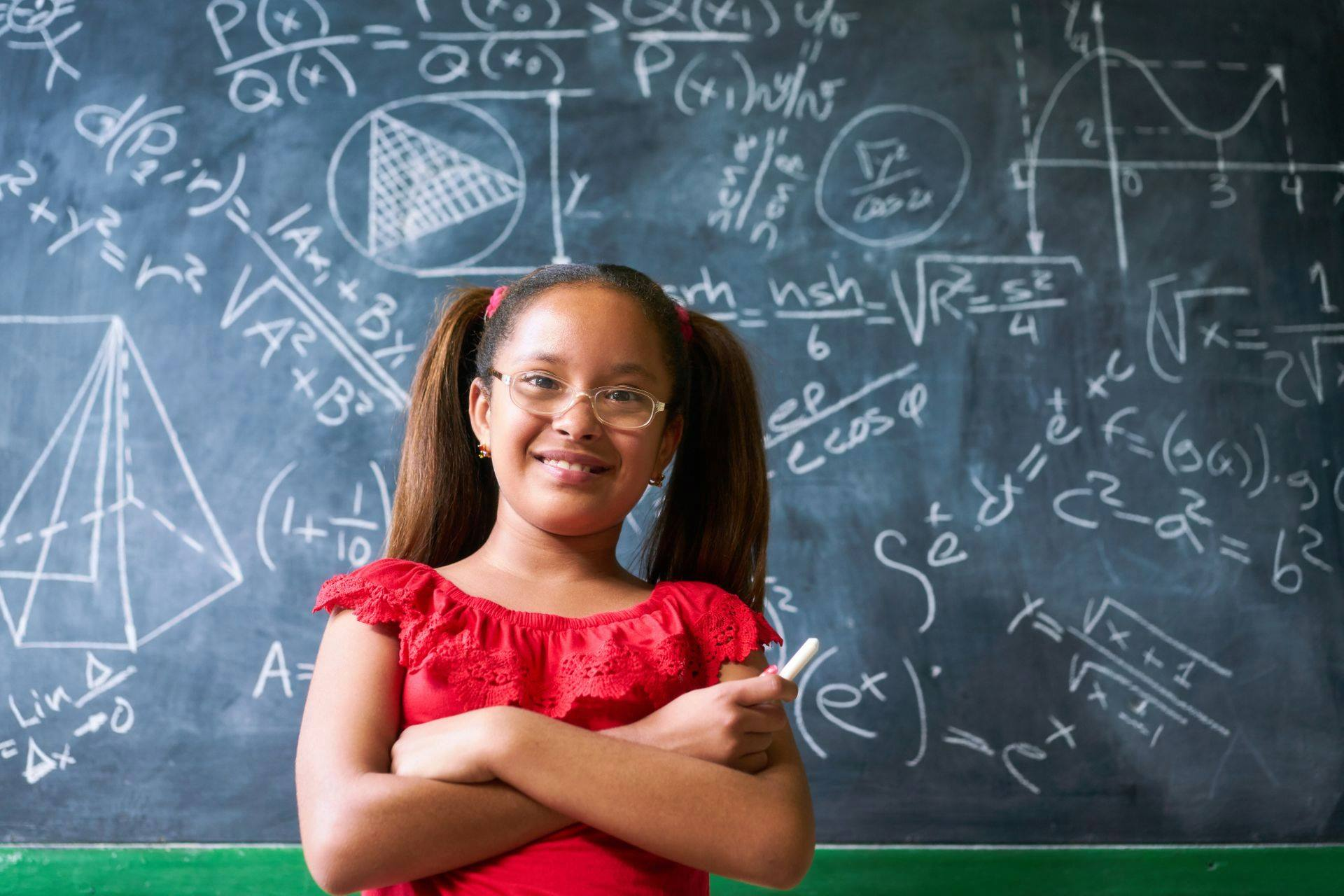 a girl with a red shirt and pigtails in front of a chalkboard
