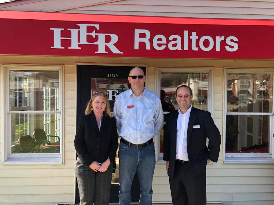 HER, REALTORS® team standing in front of a HER, REALTORS® office