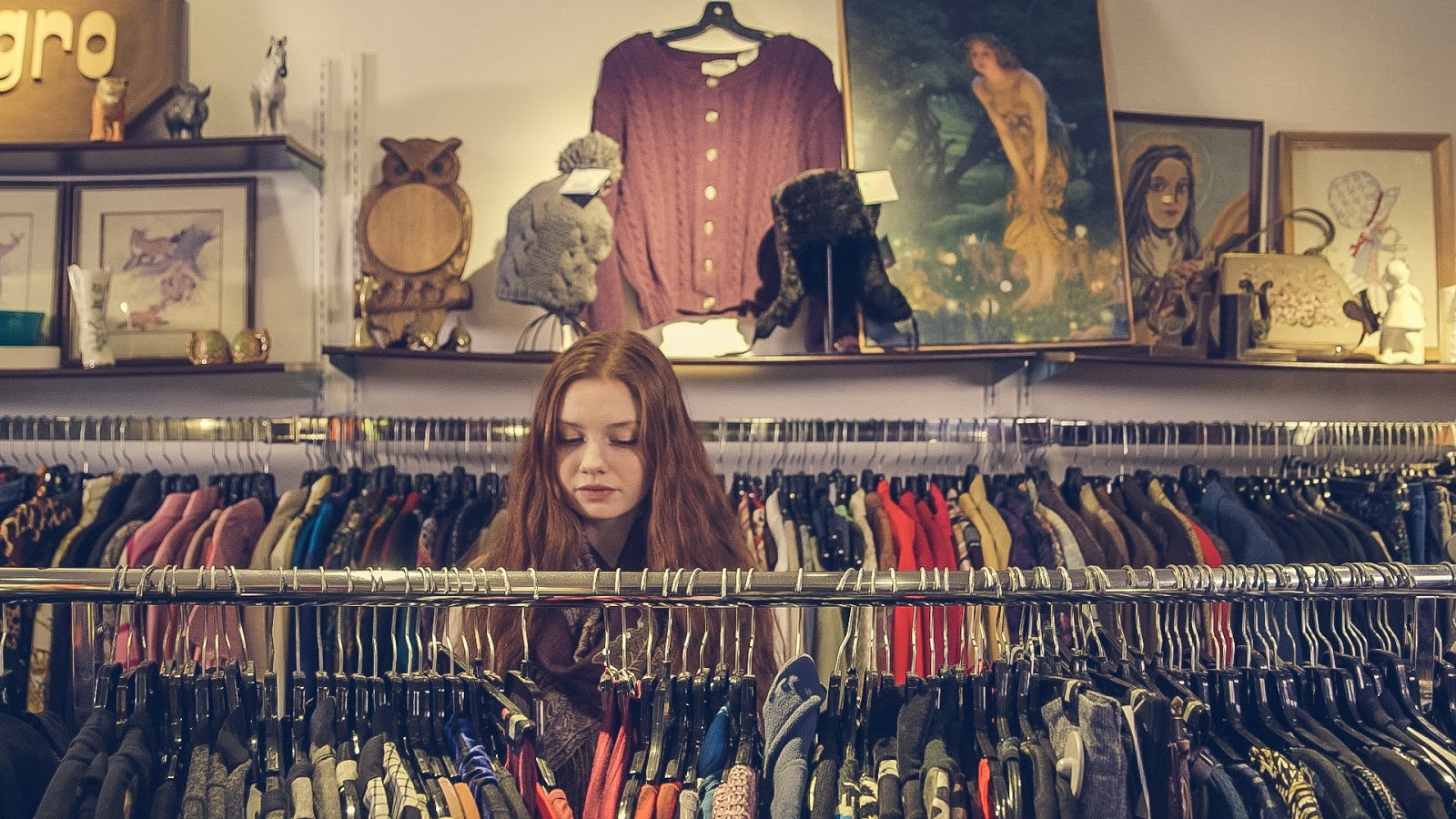 A young girl stands at a clothing rack shopping at a thrift shop.