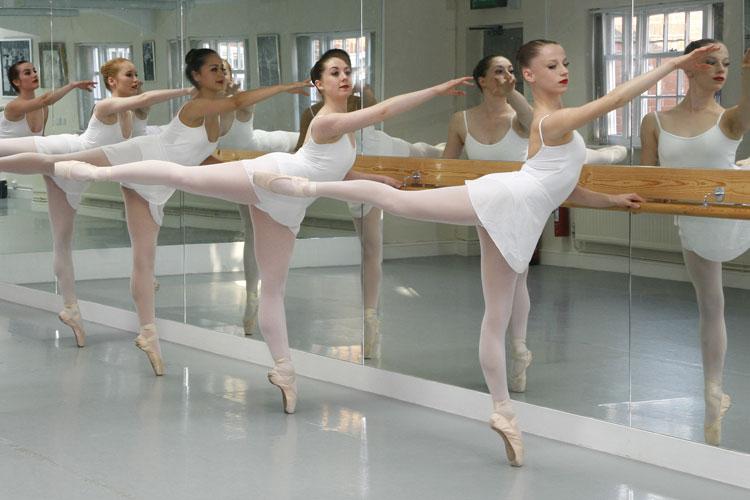 ballerinas stretching next to a mirror