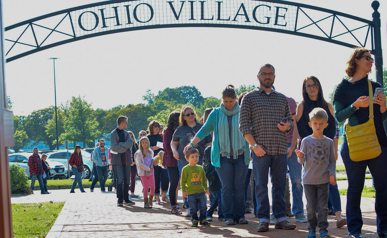 """People waiting in a line under a sign that reads """"Ohio Village"""""""
