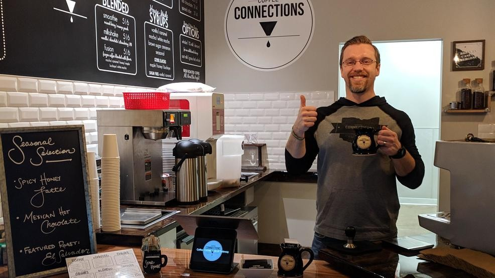 The owner of Coffee Connections in his first cafe in Hilliard, holding a mug of coffee and giving a thumbs up