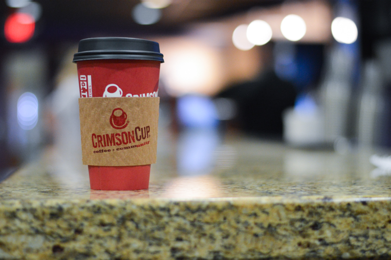 A red portable mug from Crimson Cup Coffee on a counter