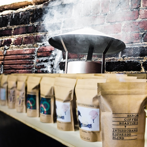 Bags of coffee from Akron Coffee Roasters in front of a rugged brick wall