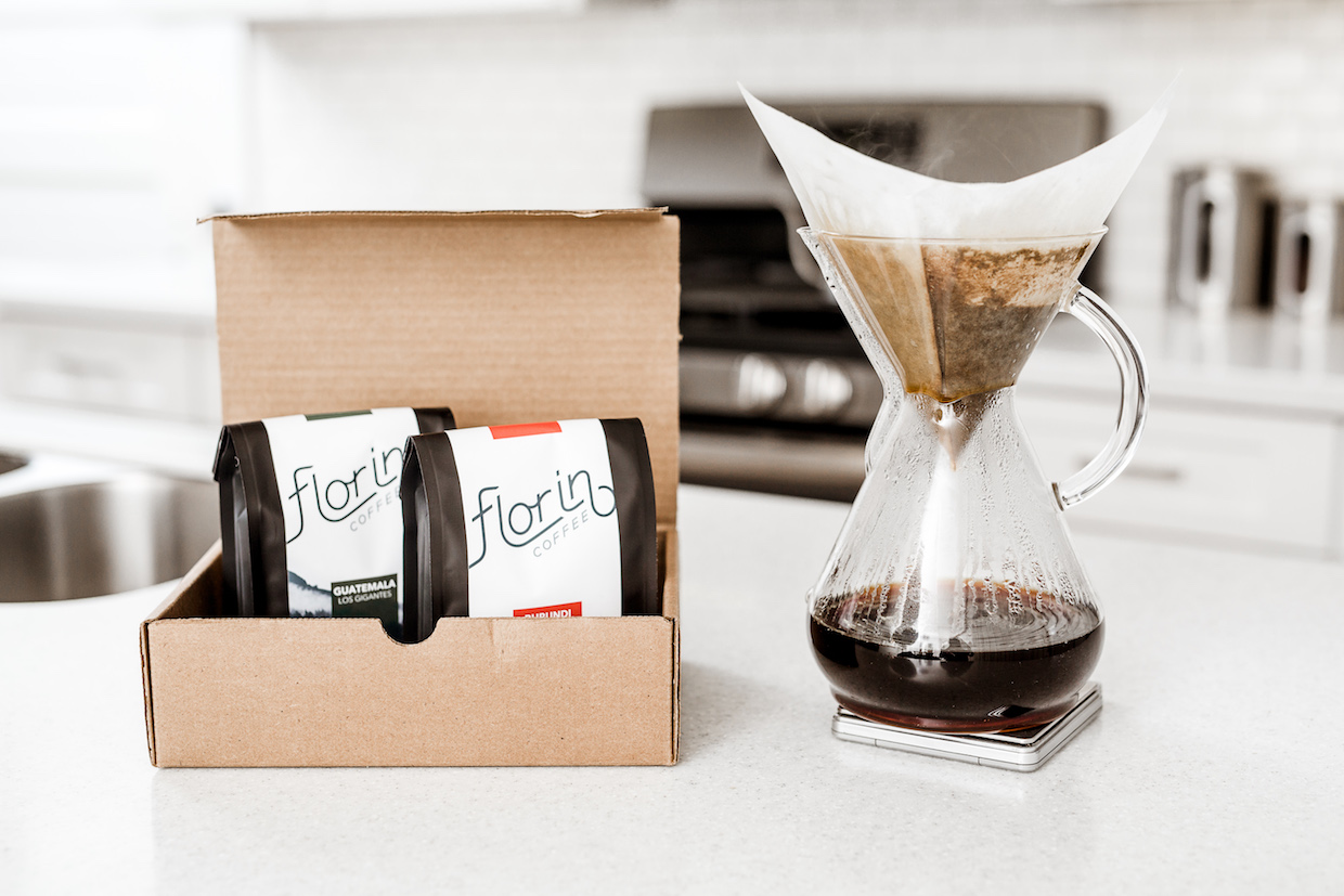 Packaged Florin Coffee in a cardboard box next to a hand-brewed pot