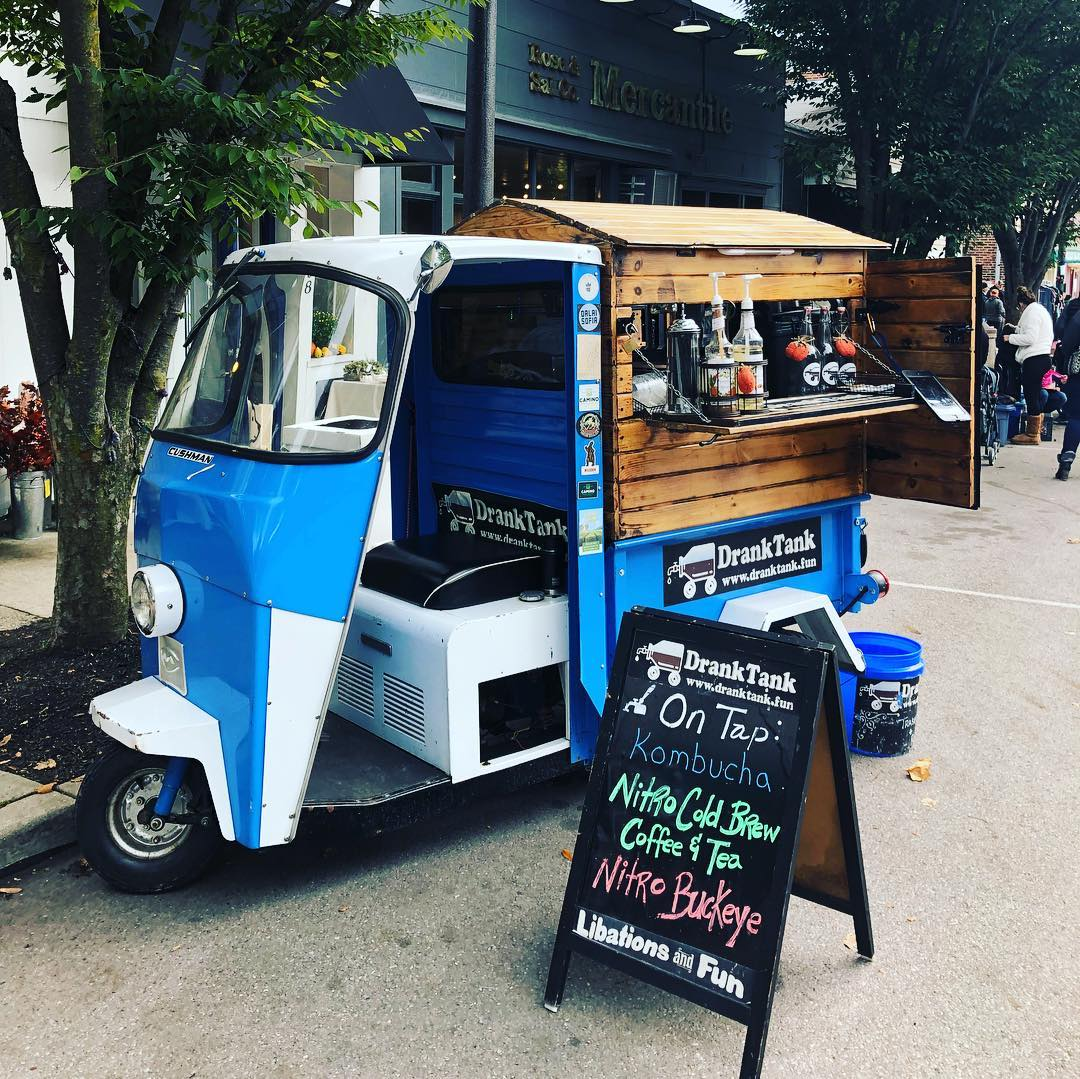 A moped with a rustic wooden coffee vending station attached to the back