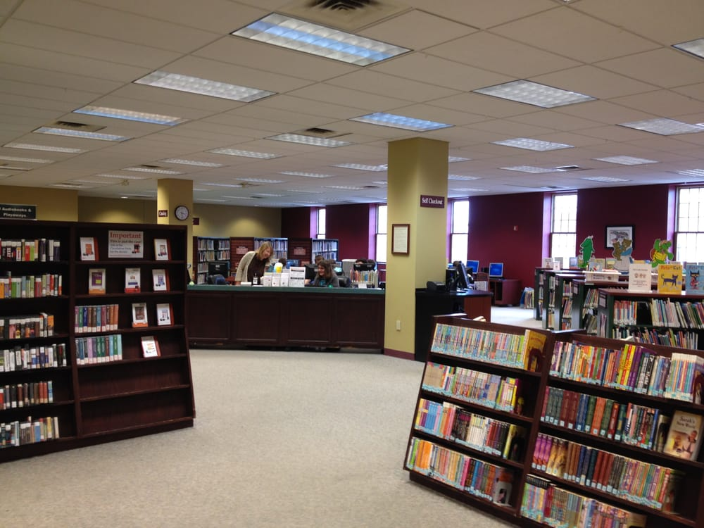 neat shelves are arranged through the red and gold main room of the lancaster, OH fairfield county library