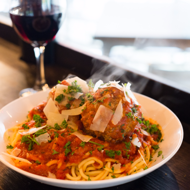 warm spaghetti and meatballs sits beside a glass of red white at one of upper arlington's best italian restaurants