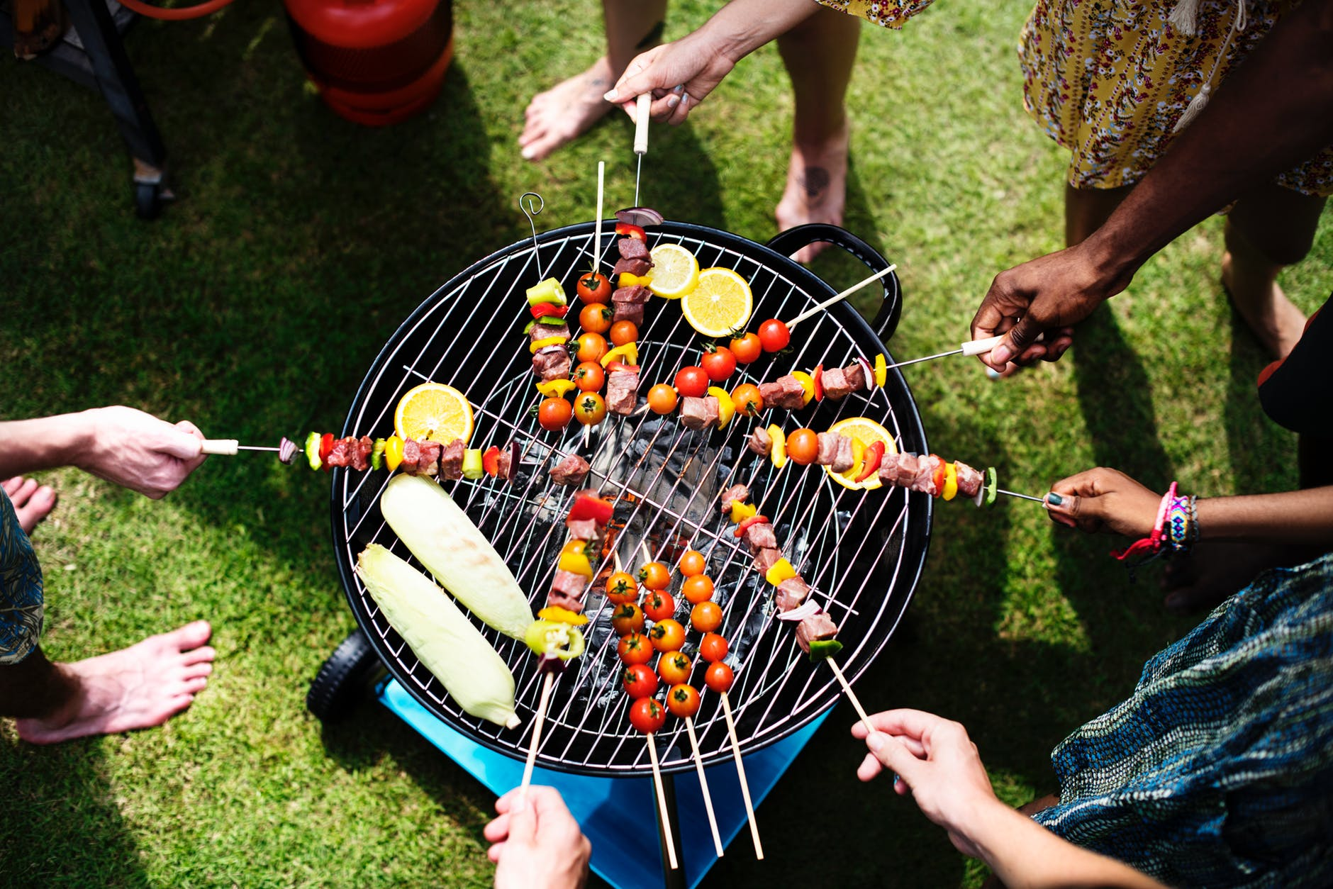 people cooking skewers over a grill at a cookout