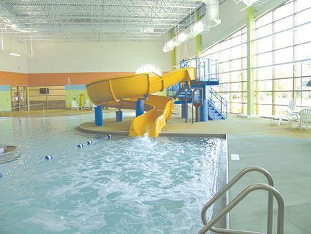 Yellow water slide splashes into indoor swimming pool