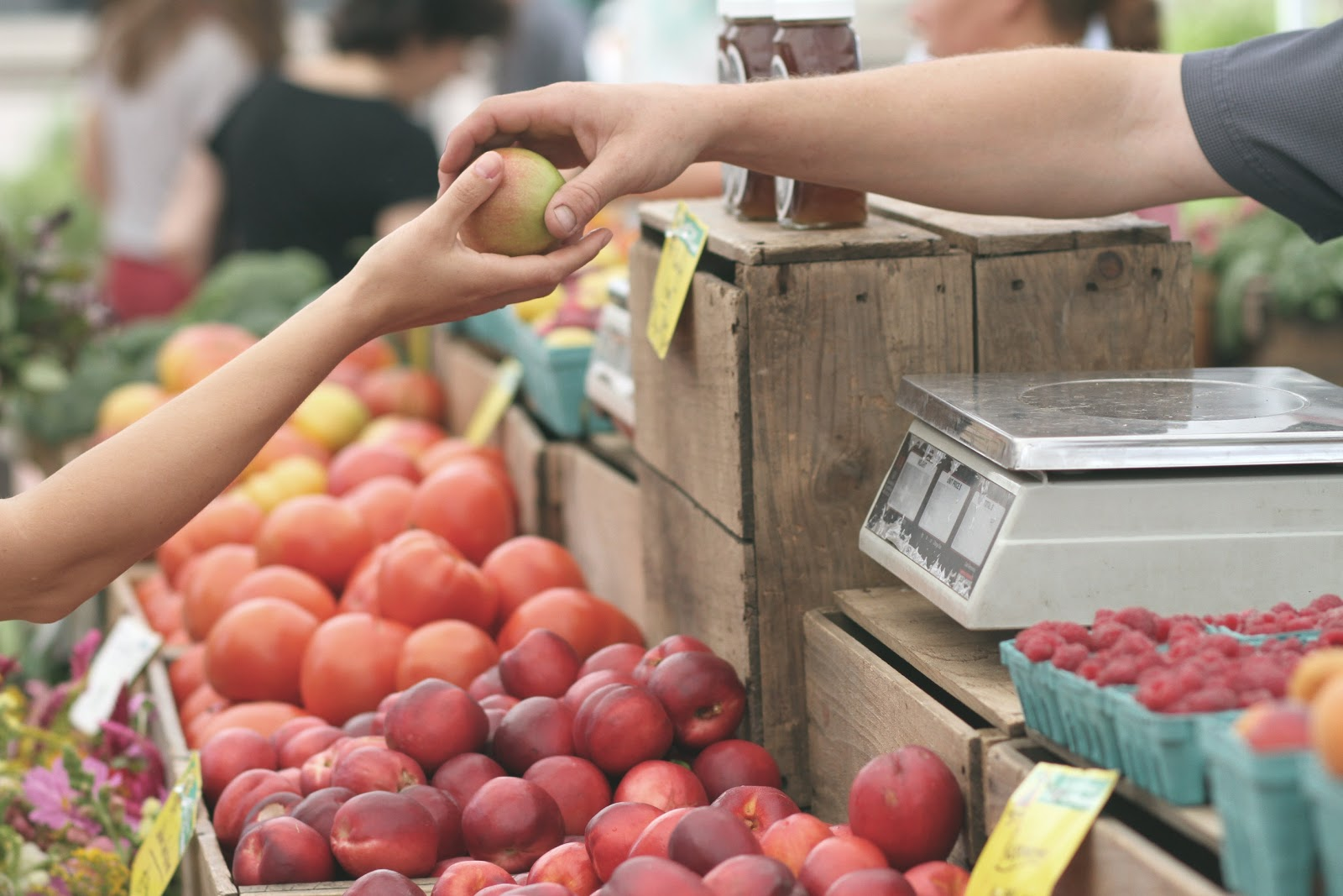 various fruit at market, with one person handing another an apple