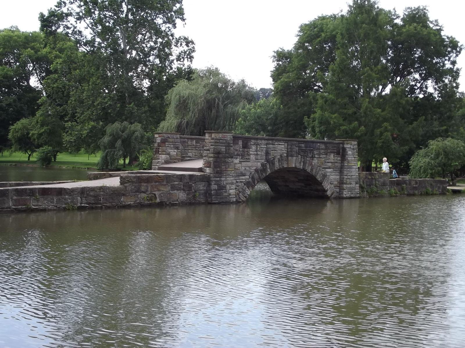 stone bridge over water with surrounding trees
