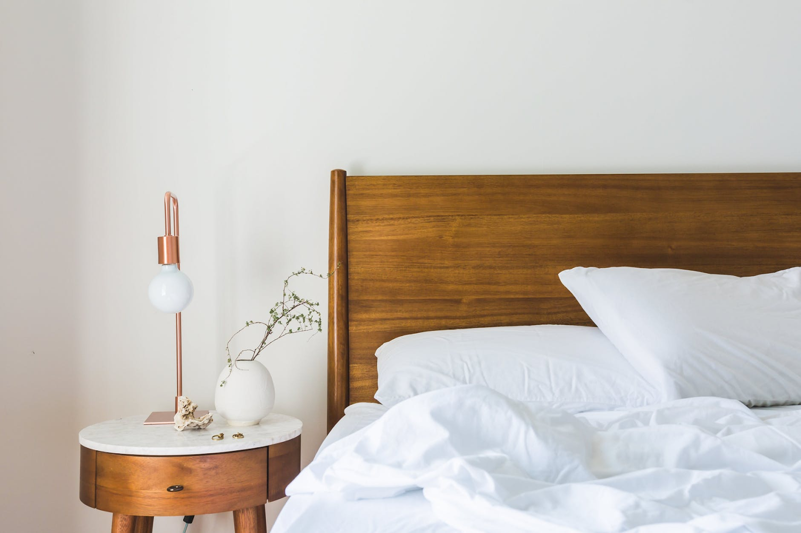 A bed with a natural headboard and a thick rumpled comforter
