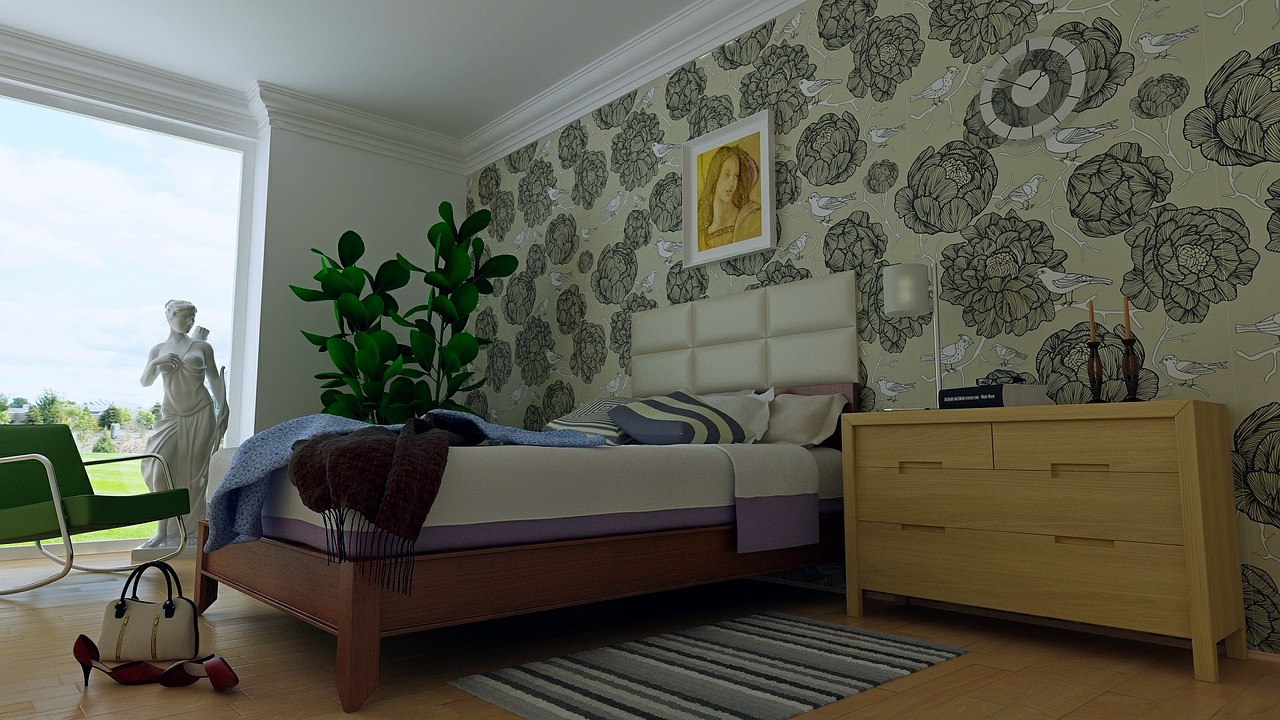 Floral wall paper covers the wall behind the headboard of a bed
