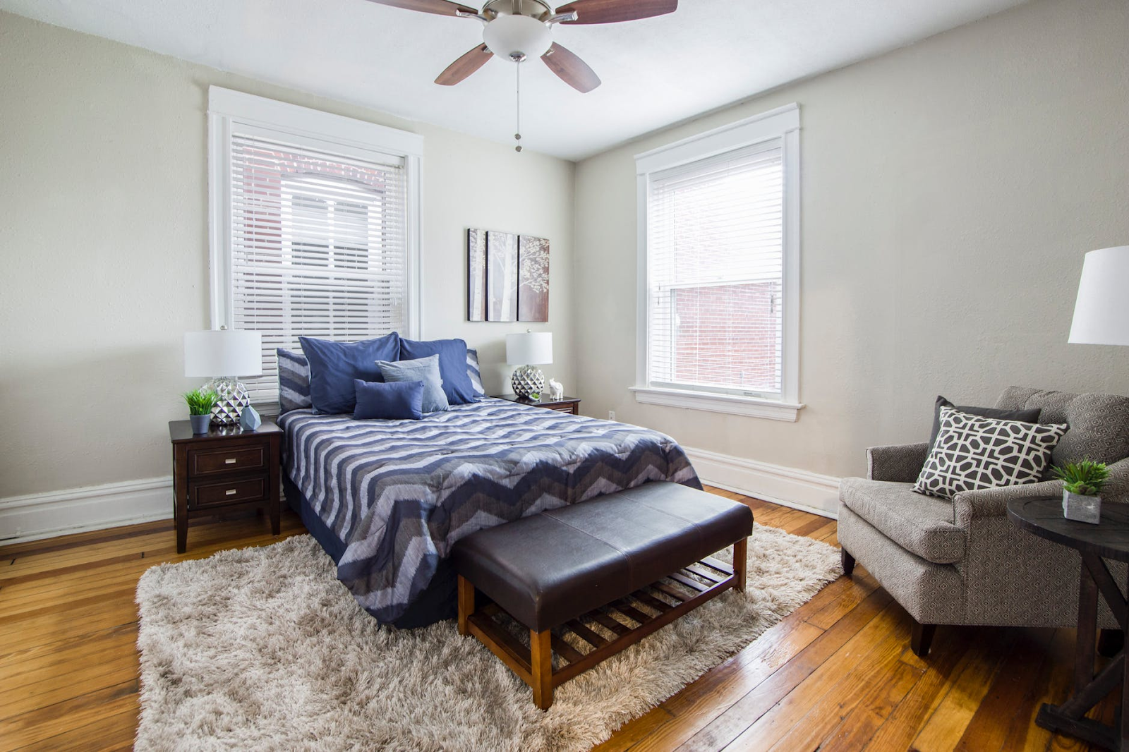A bedroom with a cozy bed, a rug, and a plush arm chair