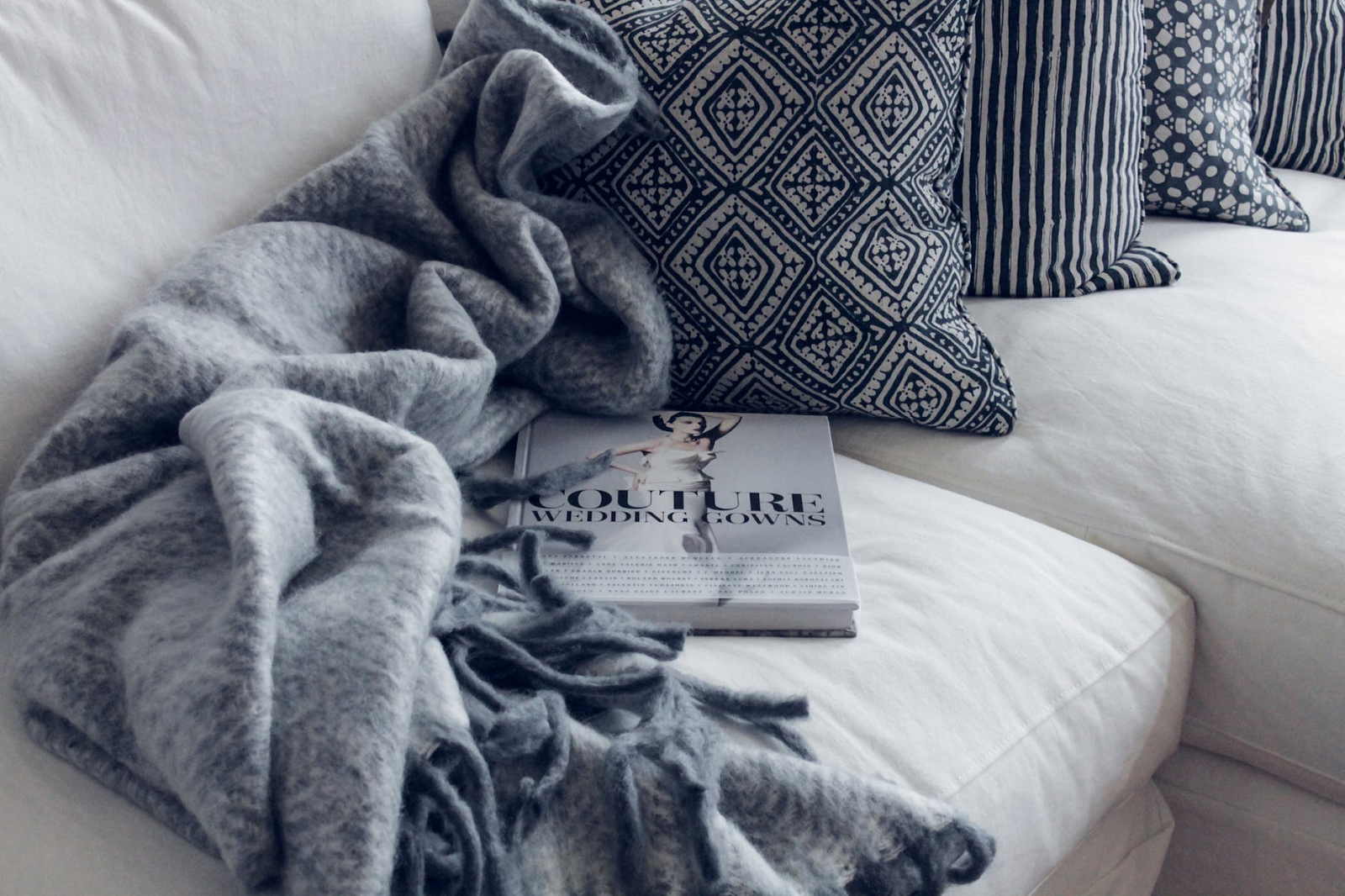 A throw blanket and a book resting on a sofa