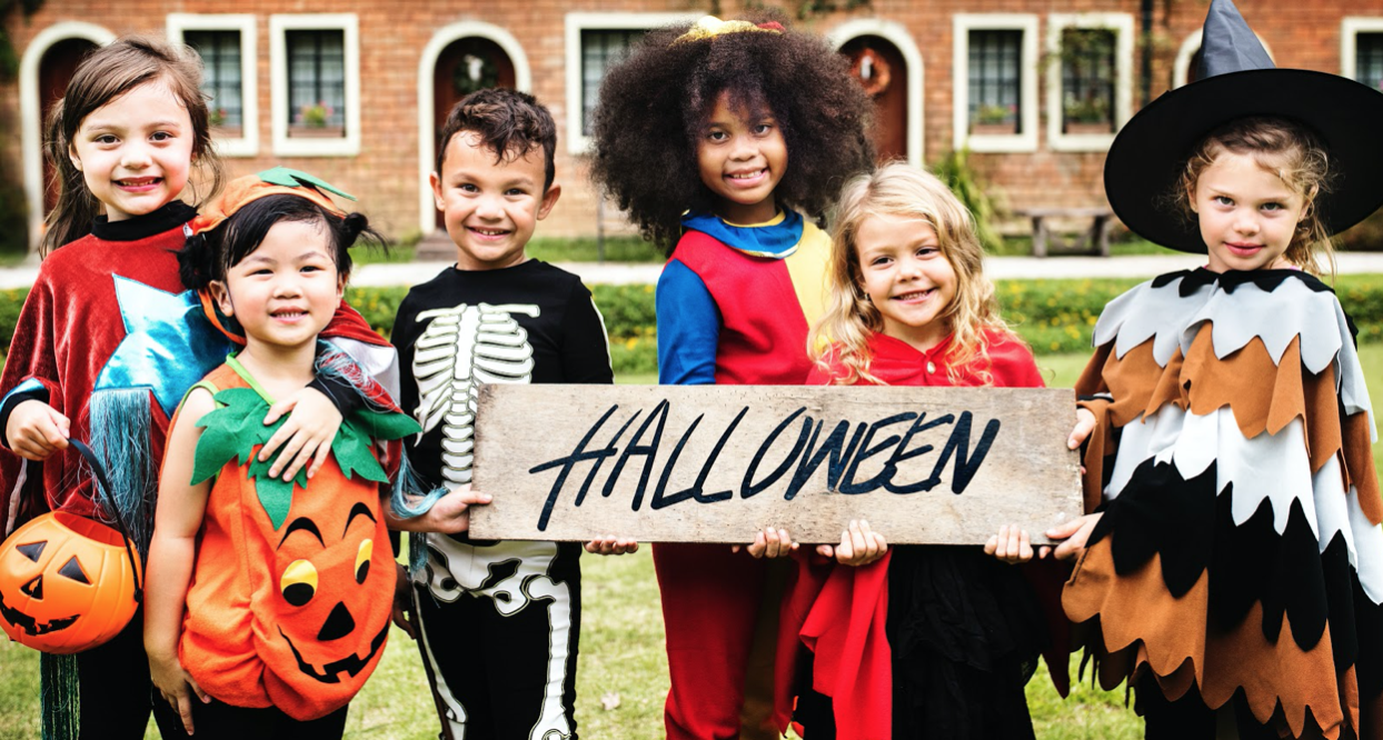 children in costume holding a halloween sign