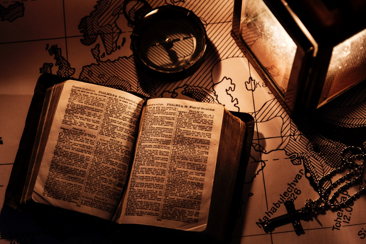 an old book open on a map beside a compass, a rosary, and a lantern