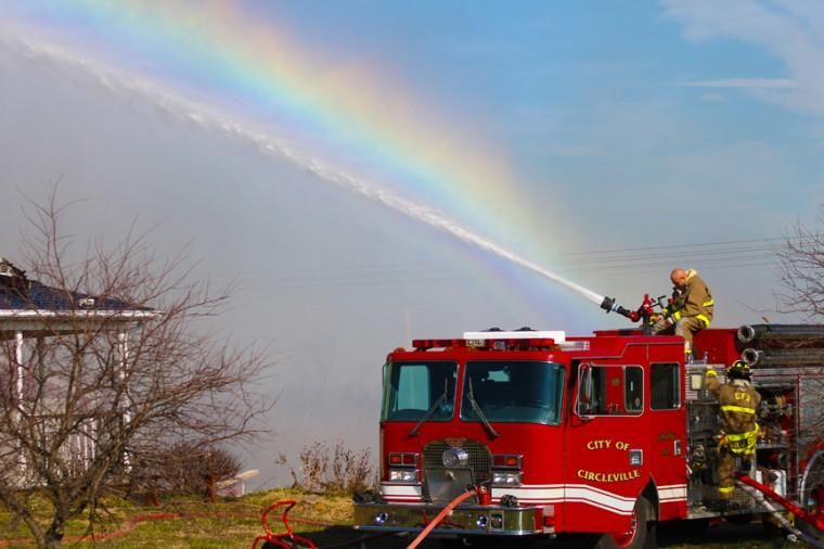 Firefighters put out a fire with a rainbow in the background