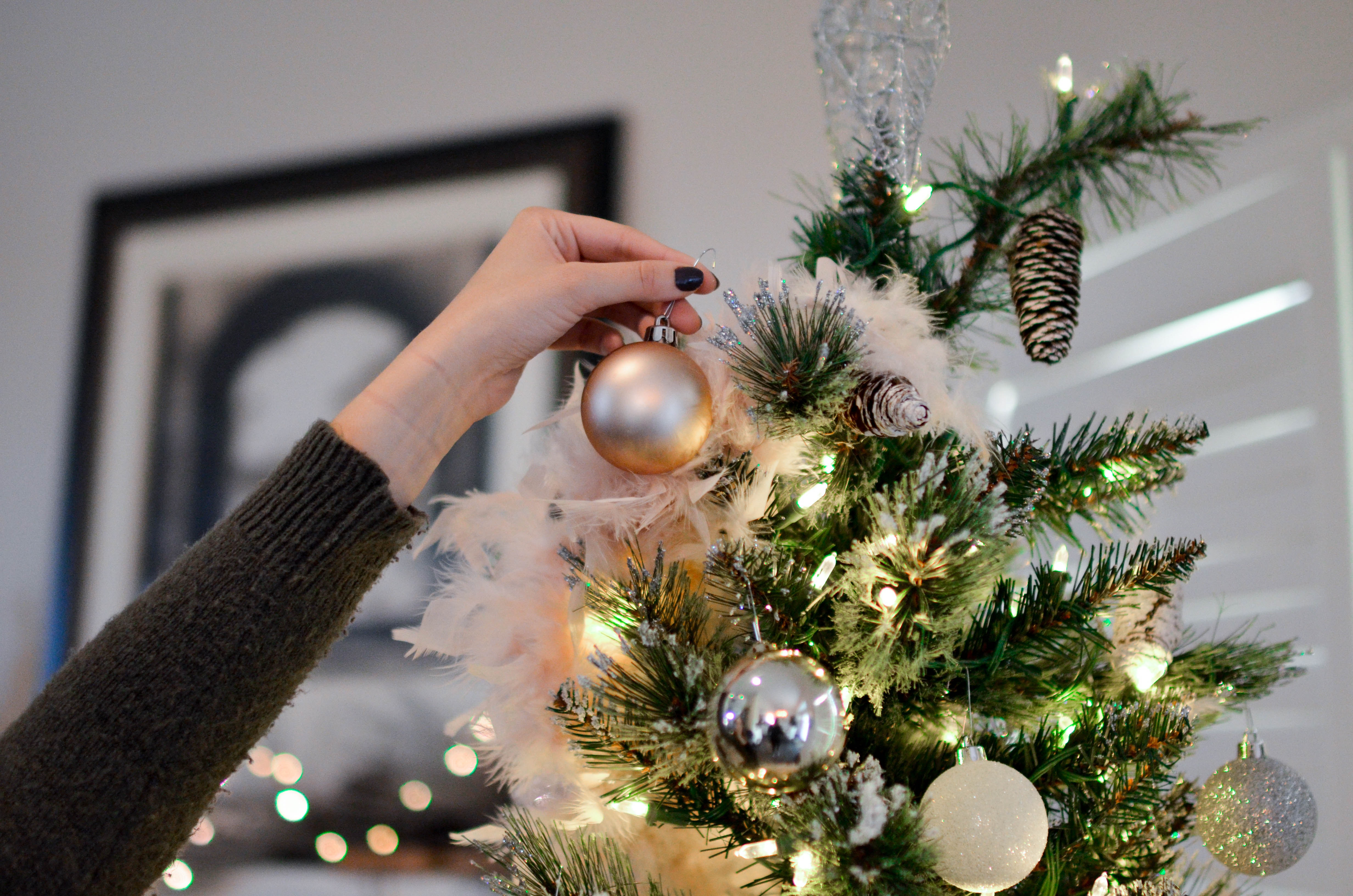 Hanfing a golden ornament on a tree with pinecones and christmas lights