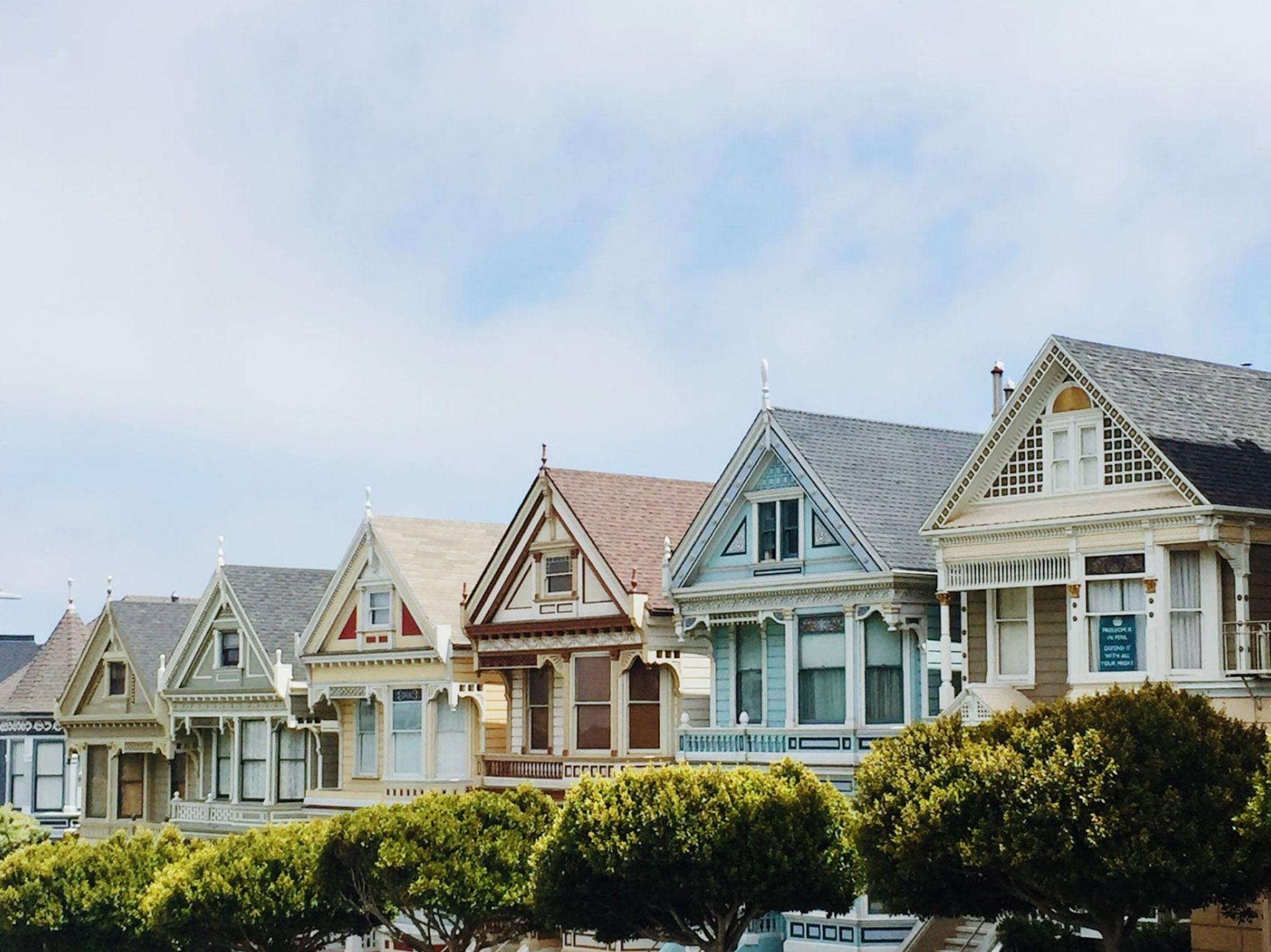 suburban homes under a pale blue sky