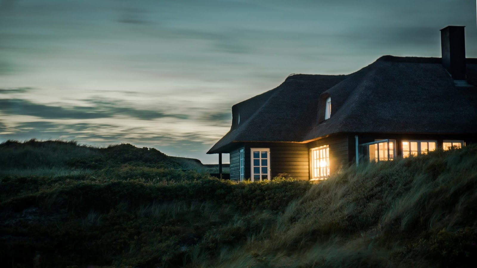 a home sitting on a hilltop at dusk