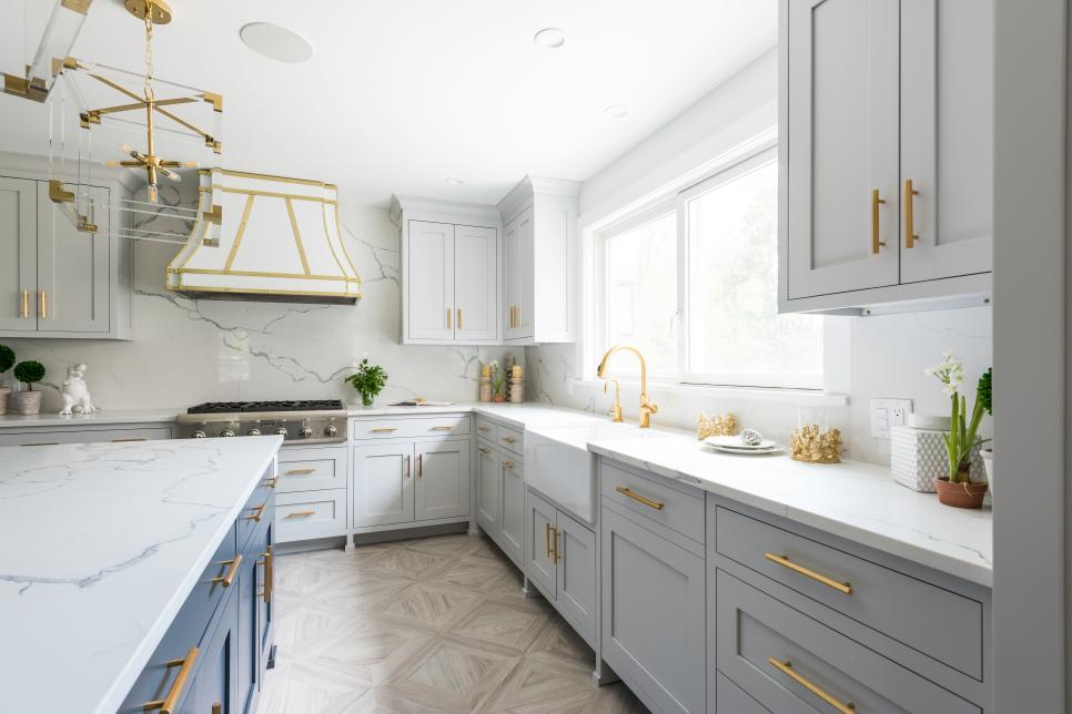 HGTV interior designed kitchen with golden highlights and a marble wall with large scaled marble patterns.