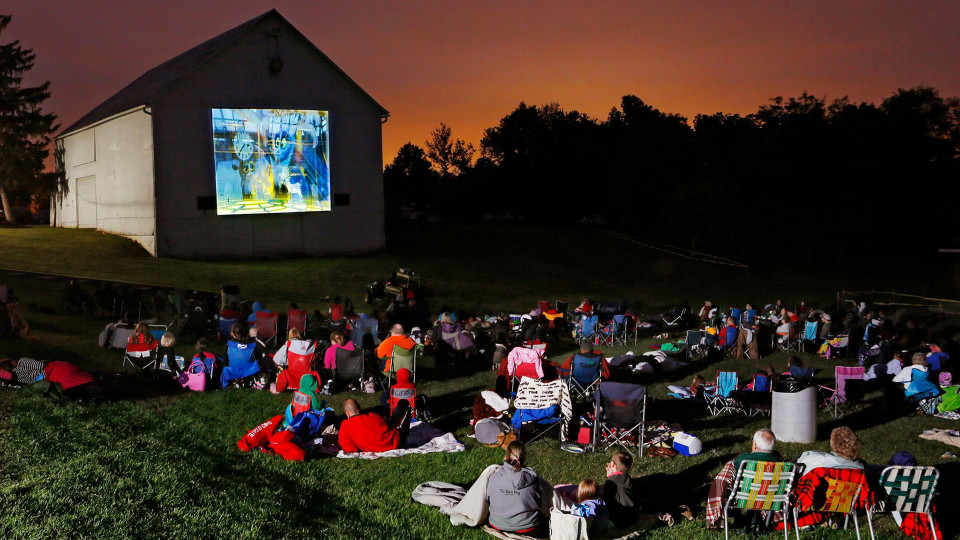 A movie is being projected on the side of a building as a large crowd rests in a lawn watching.