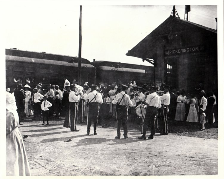A vintage photo of a marching band preparing for a parade