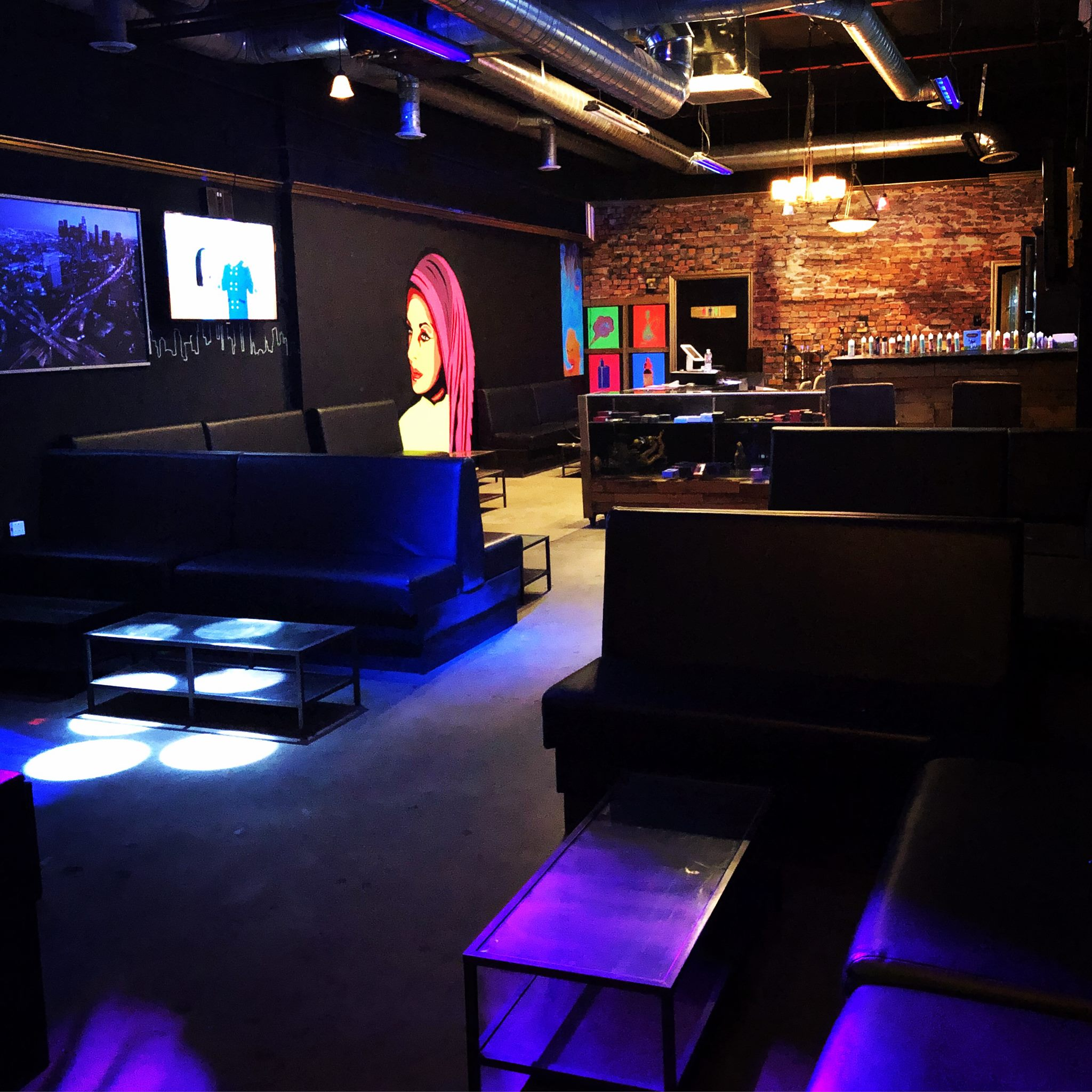 Interior of the Hookah spot is lit dark with a black light and an exposed brick wall in the back
