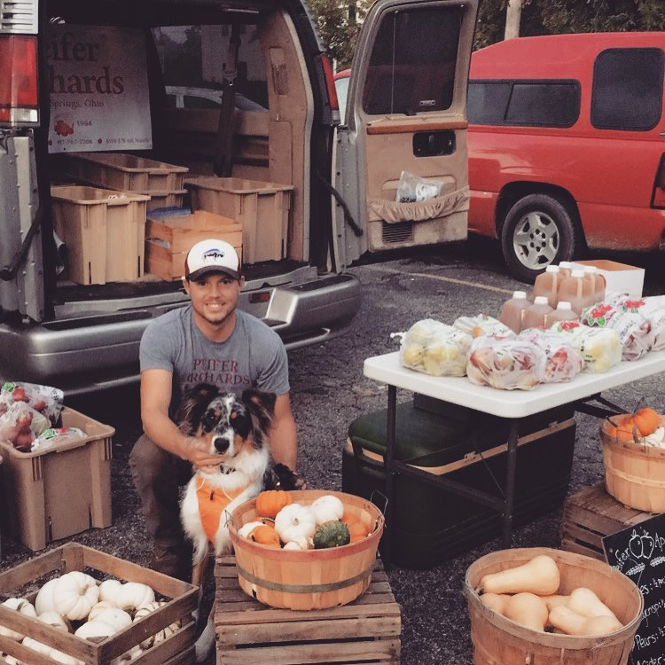 A man and his dog sit behind a table of bagged apples at a farmers market