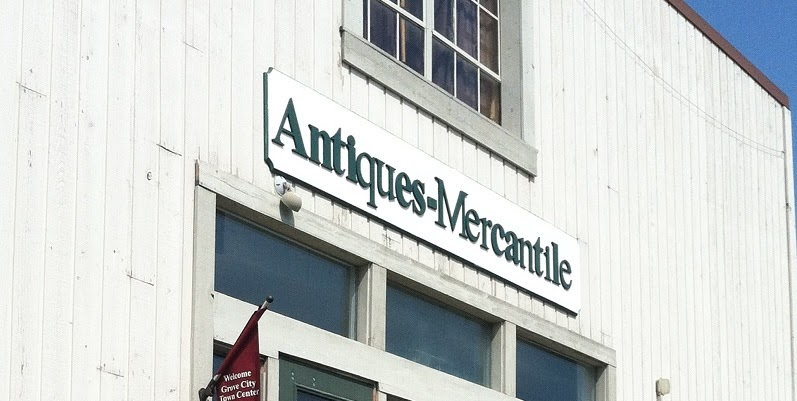 White, barn-like store front of an antique shop in Grove City, Ohio called Antiques-Mercantile