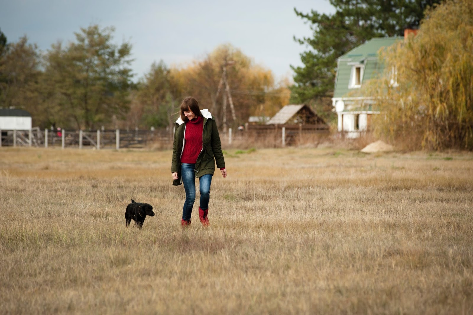 A woman in fall clothing walks through a rural field of brown grass with her black lab