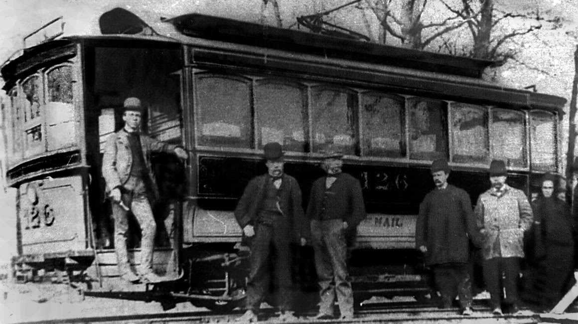 A black and white photograph depicting some of the first settlers of Grove City posing in front of a trolly