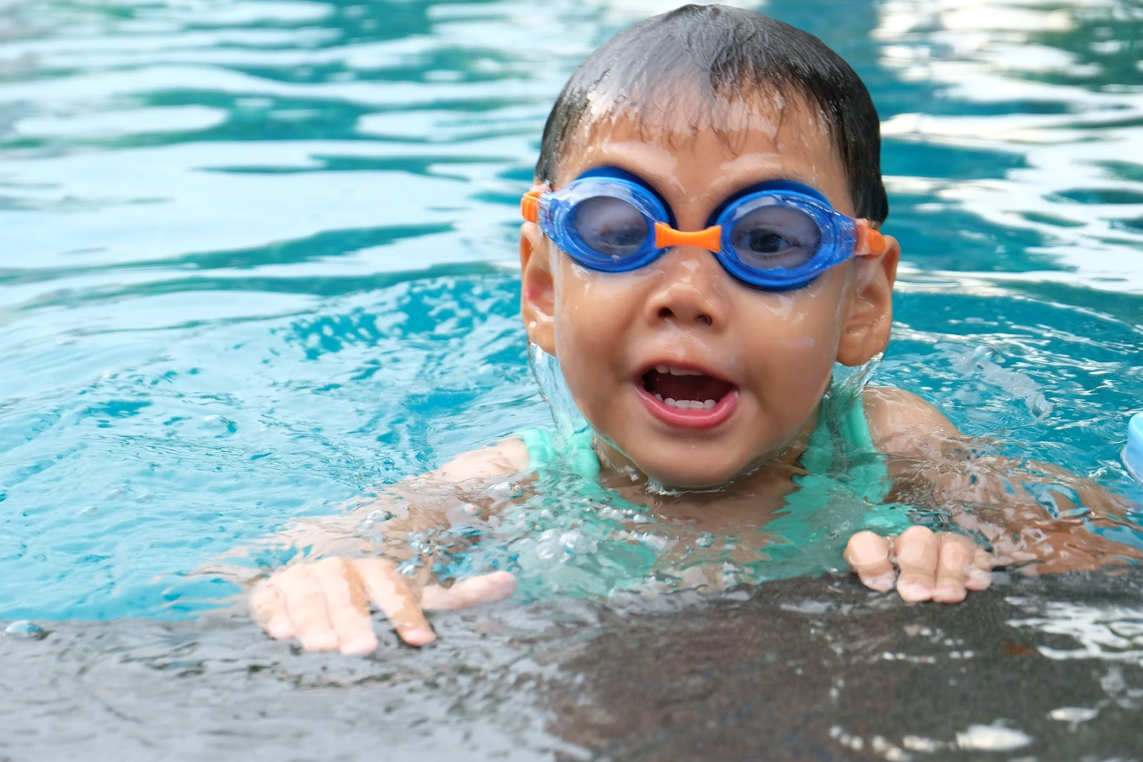 a child wearing swimming goggles, popping their head out of some pool water