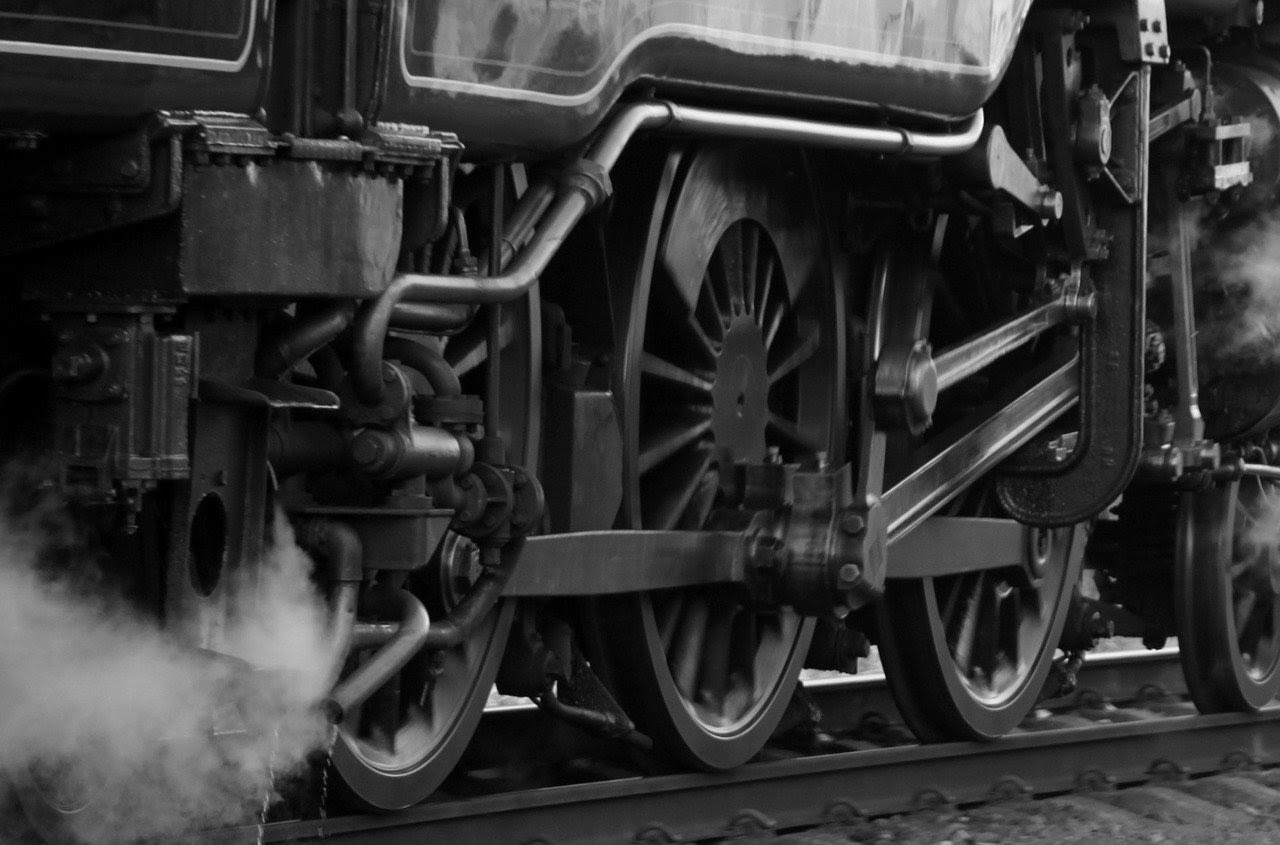 black and white image of an old-fashioned train on train tracks